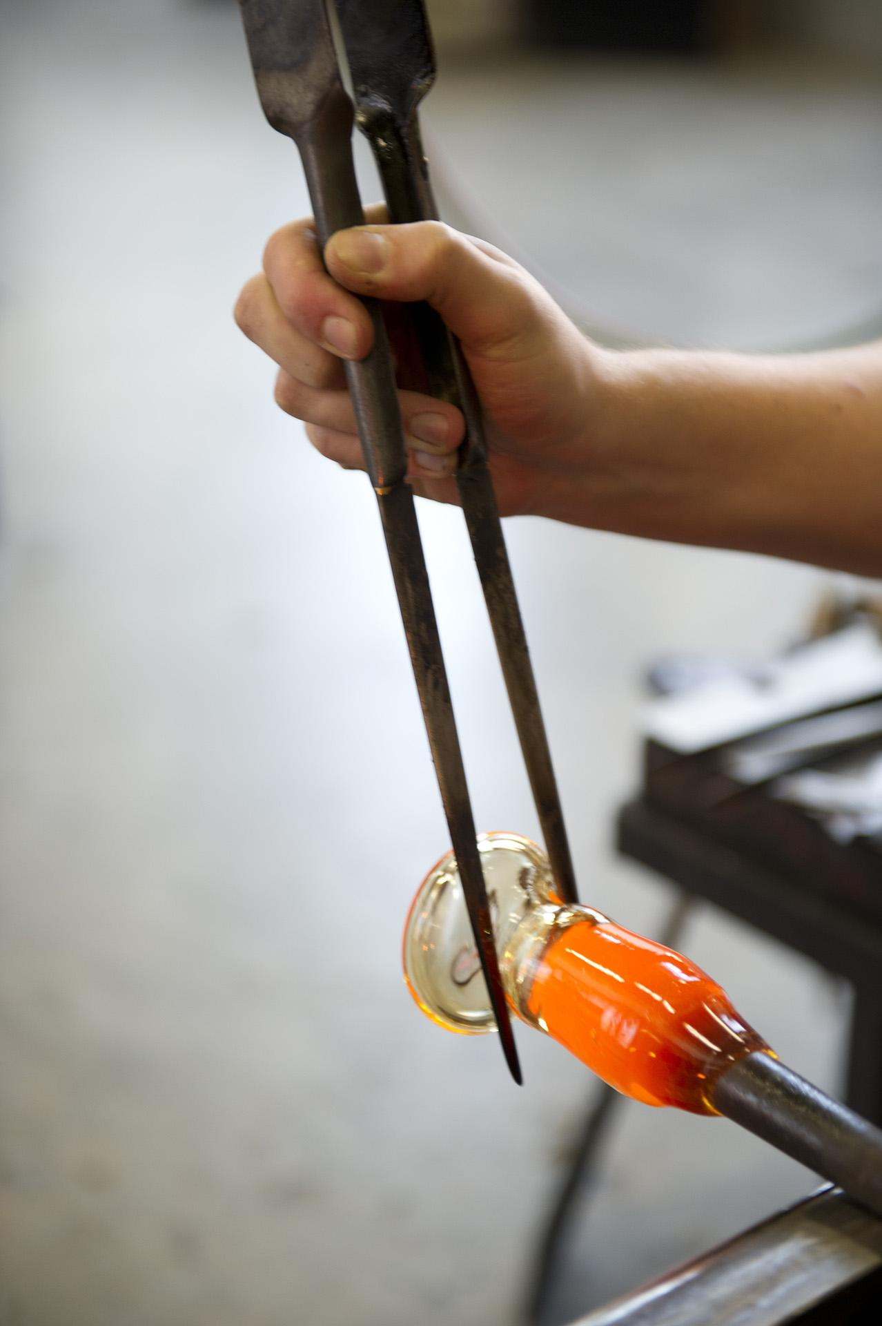 Artist shaping hot class using metal tools